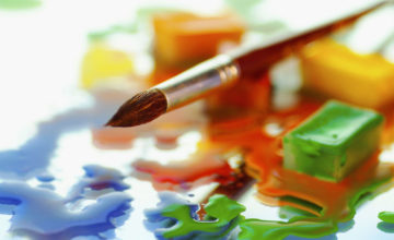 Close-up of watercolor paint cubes and a paintbrush