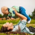 Beautiful young mother and her son are having fun outdoors in sunshine