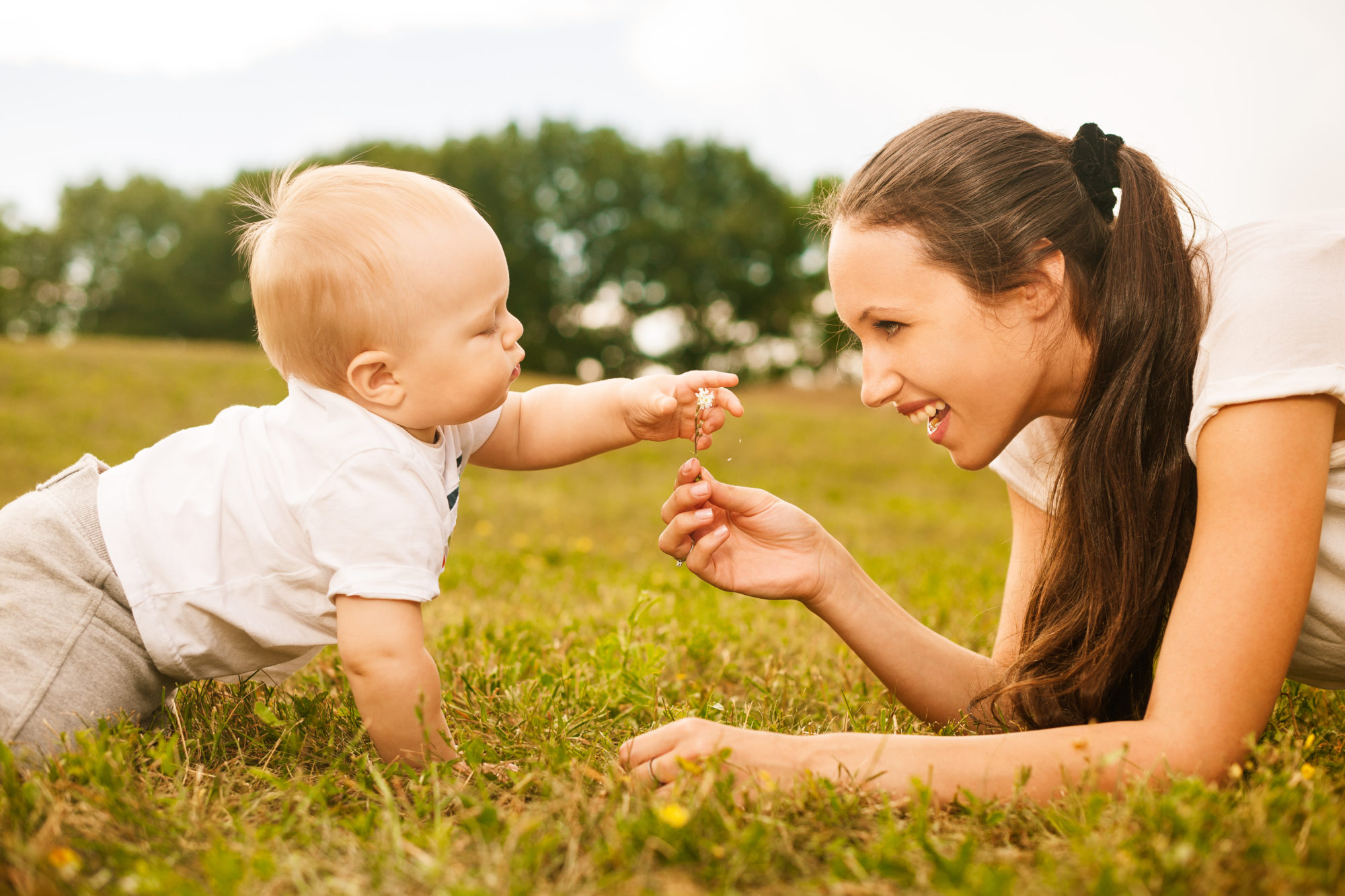 mother passing flower to her baby in the park