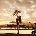 Young attractive mother and her baby boy having fun at sunset on the beach.