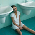 Woman Sitting on Floor in Bathroom --- Image by © Gary Edwards/zefa/Corbis