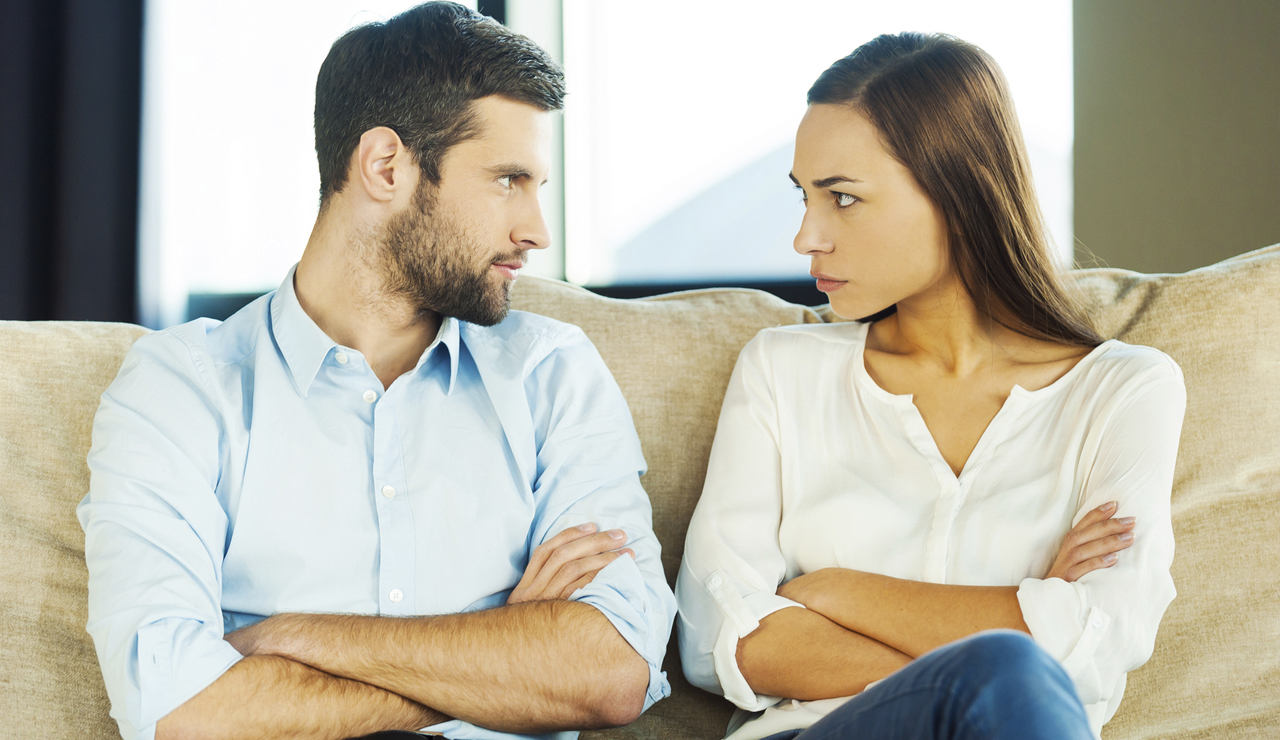 Angry young couple looking at each other and keeping arms crossed while sitting close to each other on the couch
