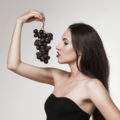 Portrait of young sexy brunette eating  grapes. Beautiful woman dressed in black posing in studio.